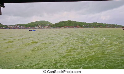 Azure Sea Single Boat Sailing in Waves against Hilly Island...