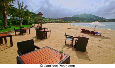 Beach with Wooden Tables Chairs Chaise-longues Boat by Wave...