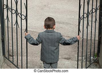 Little boy opens a wrought-iron gate