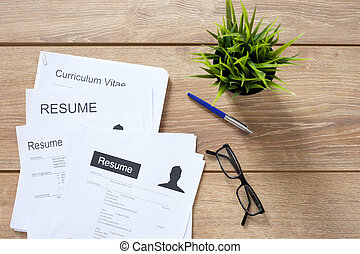Resume applications on the desk ready to be reviewed -...