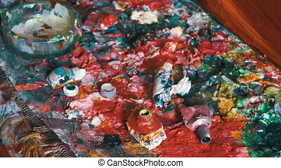 Multicolored Oil Paints on the Artist's Desk in the Picture...