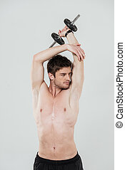 Young shirtless sportsman doing exercises with a dumbbell -...