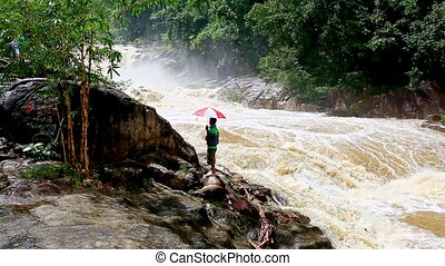 Man Stands on Rock Watches Stormy Powerful River in Mountains