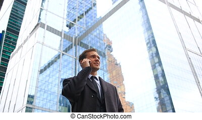 Business man in the city making a phone call with smartphone.Against the background of skyscrapers