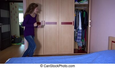 Playful mother with her daughter girl hide in closet and...