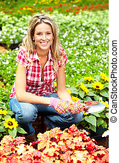 Florist - Young smiling woman florist working in the garden...