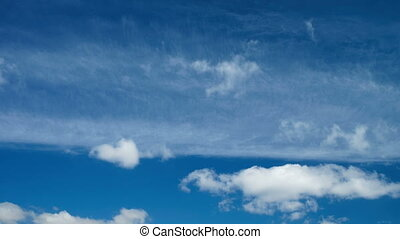 White cumulus and fleecy clouds running across blue sky -...