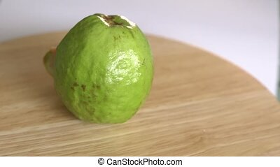 Guava with slice rotates on wooden table and white background