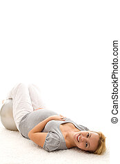 Pregnant woman relaxing on the floor after exercising