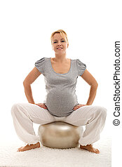 Confident pregnant woman sitting on exercise ball