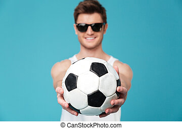 Cheerful man holding foot ball - Picture of young cheerful...