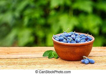 honeysuckle in bowl on table - honeysuckle berries in bowl...
