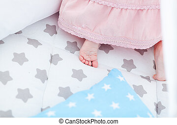 Closeup view of child feet at bed