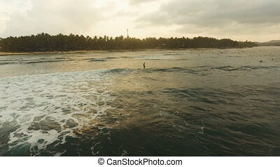 Aerial view surfers on the waves at sunset.Siargao,...