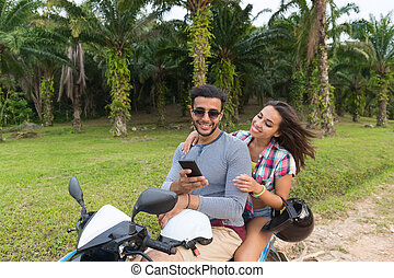 Couple Riding Motorbike, Young Man And Woman Using Cell...