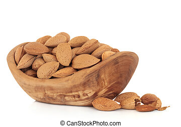 Almonds - Almond nuts in an olive wood bowl and scattered,...