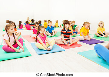 Kids doing butterfly exercise sitting on yoga mats -...