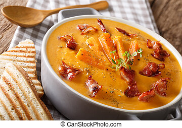 Sweet potato soup with bacon and herbs in a pan macro....