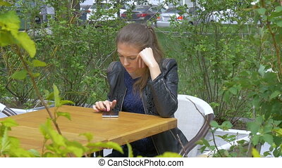 Sad beautiful girl sitting at a table in a cafe. Reads sms...