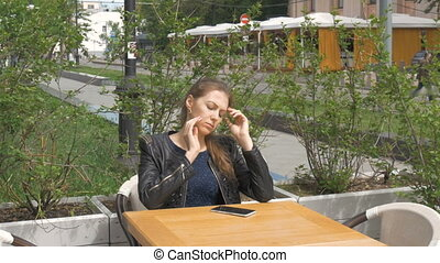 Sad beautiful girl sitting at table in cafe. Reads sms on a...
