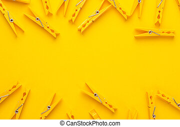 plastic clothes pegs on the yellow background with copy...