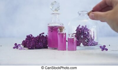 Lilac essence vials - Someone hand placing corc in lilac...