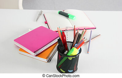 Closeup of white desktop with notepads, pen and other items....