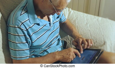 Elderly man uses tablet. Aged gray-haired male with glasses...