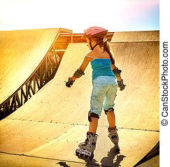 Girl riding on roller skates in skatepark. Backlit on...