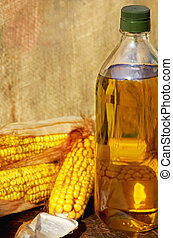 Yellow corn and oil. - Yellow corn and bottle of oil.