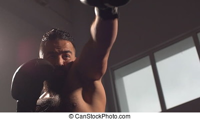 A professional boxer strikes a crushing blow at a boxing training session. Slow motion