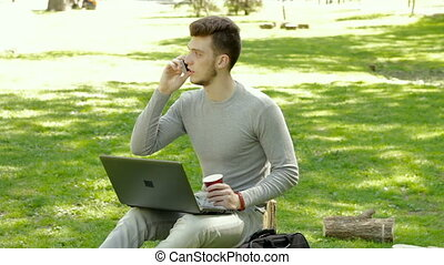 guy in the Park talking on the phone and drinks coffee with laptop