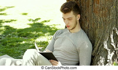 student sits in the shade under a tree in the Park and makes notes in a Notepad