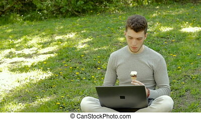 guy sitting on the grass with laptop and eats an ice cream cone