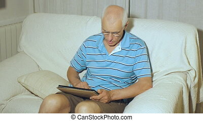 Elderly man uses tablet. Aged gray-haired male with...