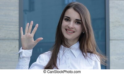 charming girl smiles at the camera and shows gesture five...