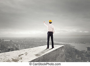 Businessman with helmet indicates the right direction