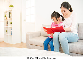mother and daughter reading story book - beautiful mixed...