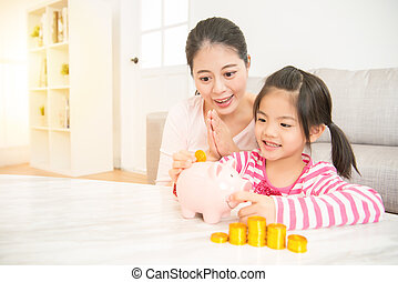 girl kid putting money into piggy bank - cute happy asian...