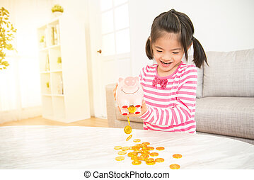 empty dump all of piggy bank money - portrait of asian girl...
