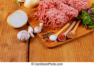 Minced beef meat with basil leaves ready for cooking -...