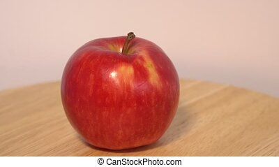 Red apple rotating on wooden table