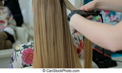 Hairdresser straightens hair of sitting woman with...