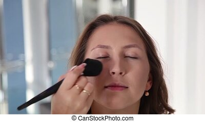 Make up artist doing professional makeup of young woman