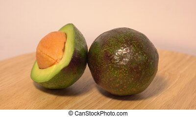 Avocado rotates on a wooden background.
