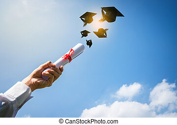 Graduates hands throwing graduation hats.
