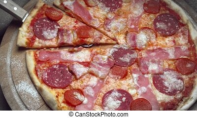 Pizza meat on a wooden plate spinning in a circle