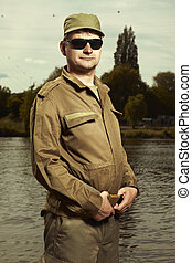 Soldier in uniform posing in front of river - Wet and dirty...
