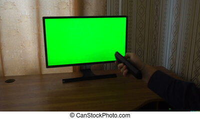 Male Hand With TV Remote Switching Channels On A Green...