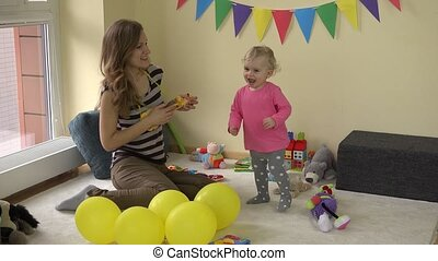 Mom playing with toy guitar and lovely baby girl dancing between toys at party